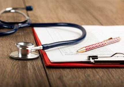 טפסים וסטטוסקופ בוועדה רפואית של ביטוח לאומי
