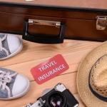 """מזוודה, חפצים וכרטיס עליו כתוב ביטוח נסיעות לחו""""ל"""