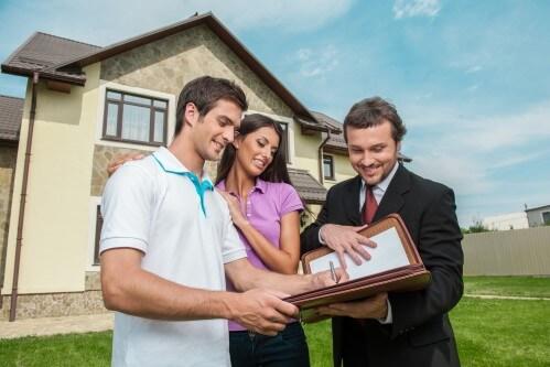 זוג עומד בפני בית שיש עליו ביטוח משכנתא