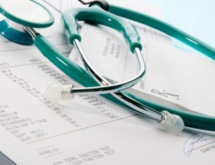 סטטוסקופ ומתחתיו חשבון של פוליסת ביטוח בריאות