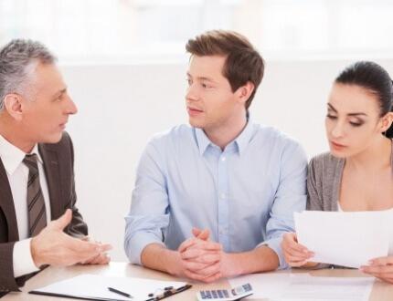 אנשים יושבים ליד סוכן ביטוח ומנסים להשוות מחירים של ביטוח משכנתא