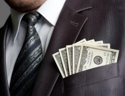 מנהל לבוש בחליפה עם שטרות כסף בכיס