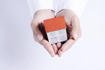 אדם מחזיק דגם מוקטן של בית בידיים