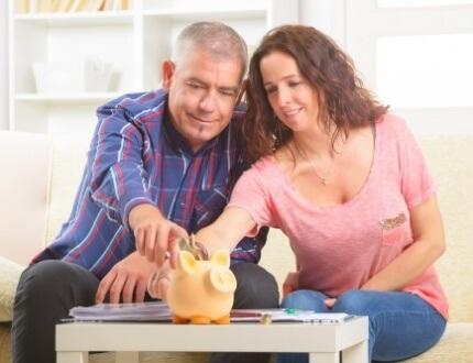 זוג יושב ומכניס כסף לקופת החסכון שלו